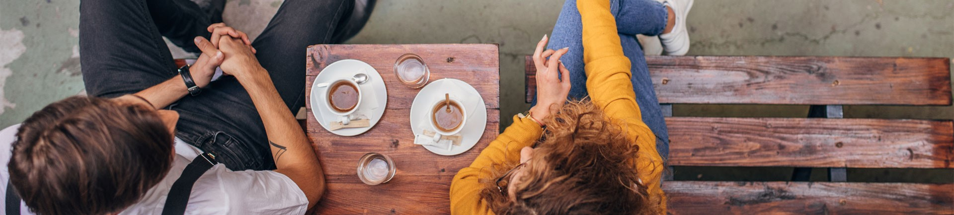 Vista de cima de um casal sentado numa esplanada a beber chá