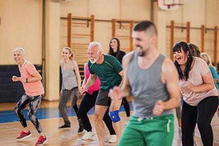 Grupo de pessoas de várias faixas etárias praticar atividades desportivas em grupo