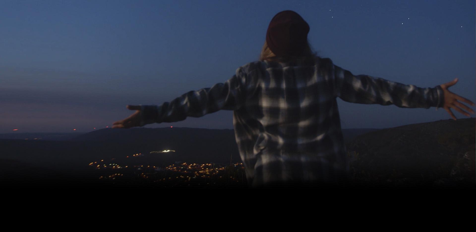 Jovem de braços abertos ao cimo de uma montanha, a abraçar a paisagem, ao anoitecer