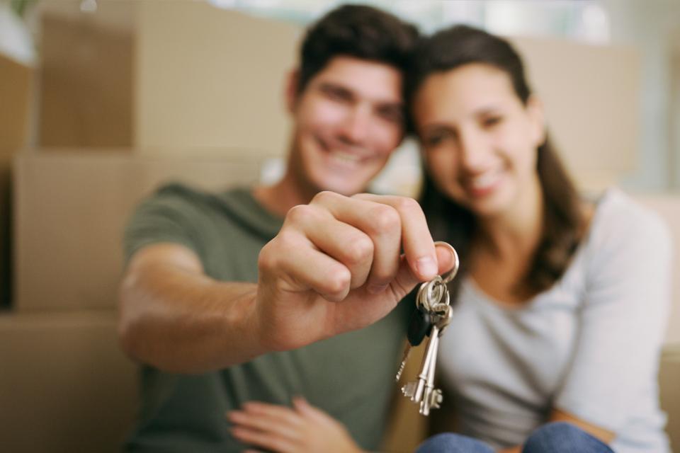 Um jovem e uma jovem desfocados. Jovem segura um molho de chaves na mão que se veem em primeiro plano.