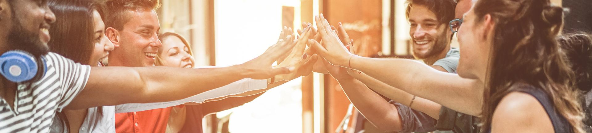 Jovens a celebrar e jovem com uma mão aberta em frente do rosto